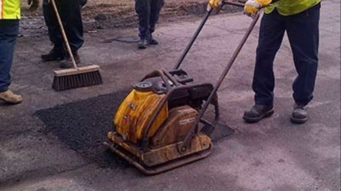 City worker compacting a pothole patched with hotmix
